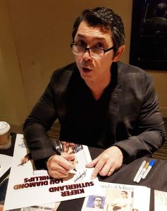 LOU DIAMOND PHILLIPS Signing a Daybill Movie Poster for Renegades image